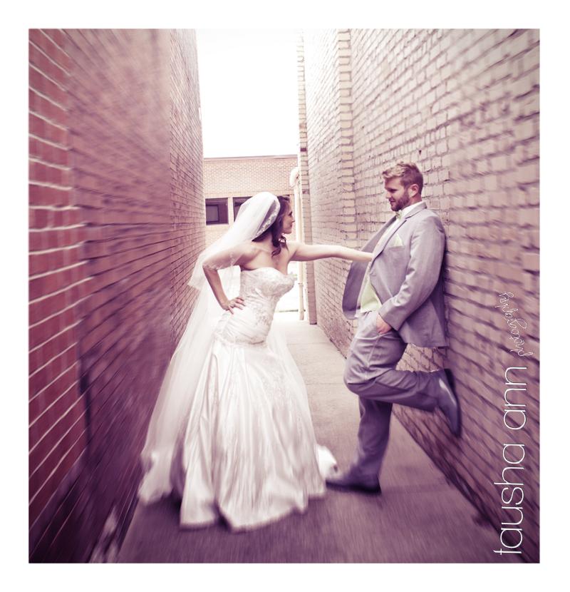 Bride pushing groom up against brick wall - Nashville TN Wedding Photography