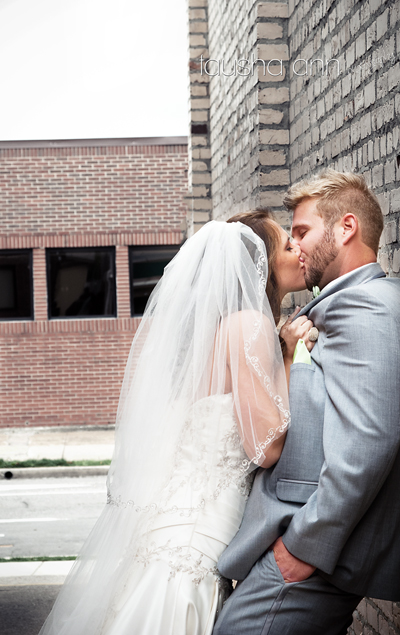 Bride Groom Kissing Up against brick wall.  Love Nashville Wedding Photography
